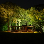 535ea4a2c07a8047be00002e_light-matters-richard-kelly-the-unsung-master-behind-modern-architecture-s-greatest-buildings_glass_house_at_night_by_steve_br